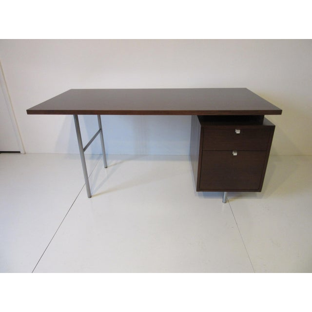 A dark walnut floating top desk with two drawers having aluminum J pulls and legs that are brushed chrome. Manufactured by...