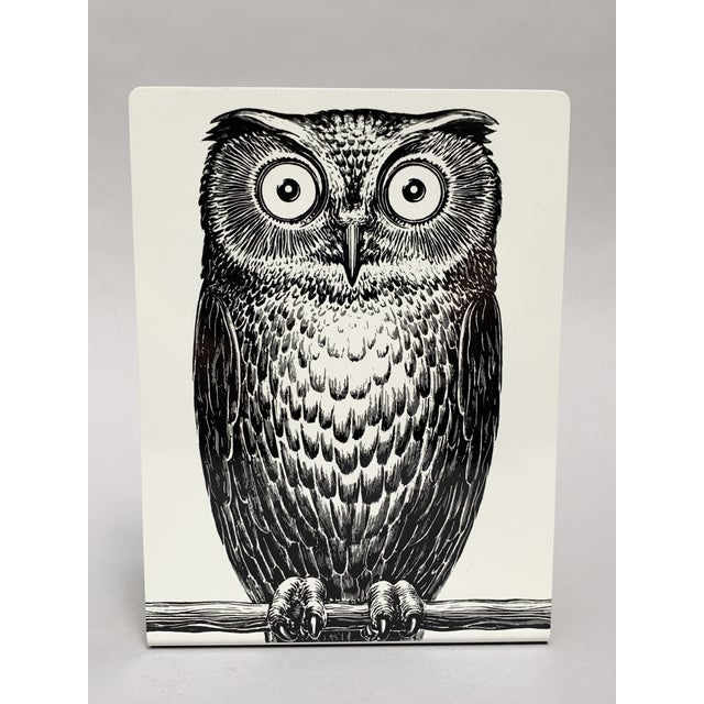 Owl bookends by Piero Fornasetti. Simple L-shaped white coated metal bookends with a quintessentially Fornasetti Owl...