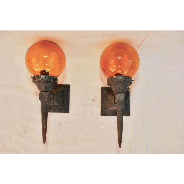 A nice pair of 1920s cast iron outdoor sconces, made of great quality cast iron. Orange globes are included.
