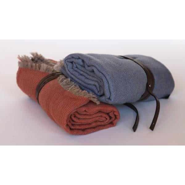 Cashmere travel throw in herringbone pattern with fringe and leather strap. In coral or denim. Priced each.
