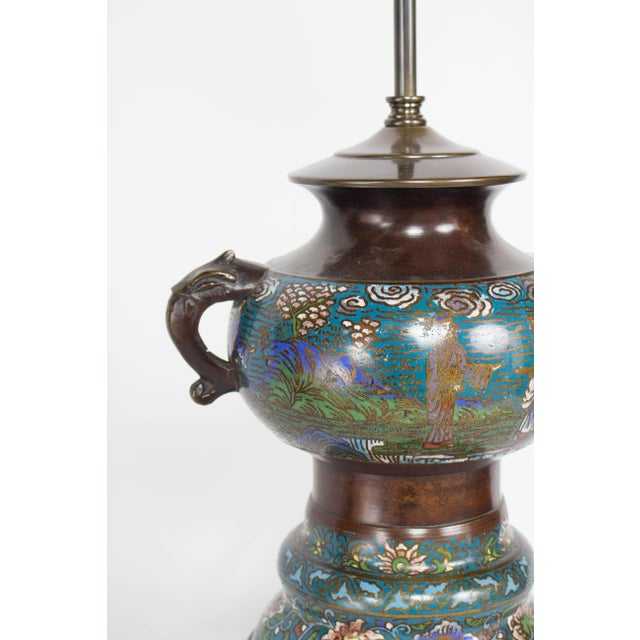 Champleve Table Lamp. Features a country scene with three people and lotus flowers around the base. Damage to center...
