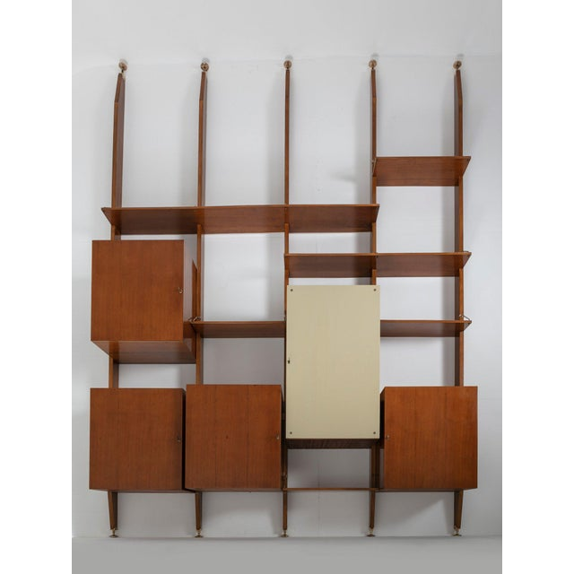 Italian 50s bookcase composed by five uprights, cabinets and shelves. Beautiful brass details and glass panel covering the...