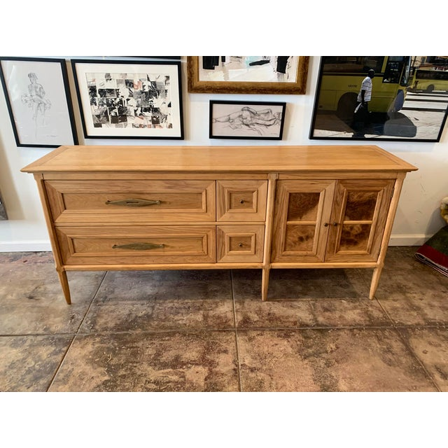 Uniquely designed by Tomlinson, the Sophisticate sideboard is made of walnut and showcases burlwood vaneer on drawer and...