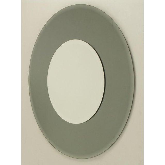 Art deco revival round smoked mirror framed around mirror. Beveled mirror frame as well as beveled interior mirror.