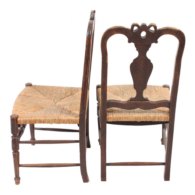 Set of four Louis XVI-style walnut chairs with rush seats and featuring a hand-carved bow and vase motif.