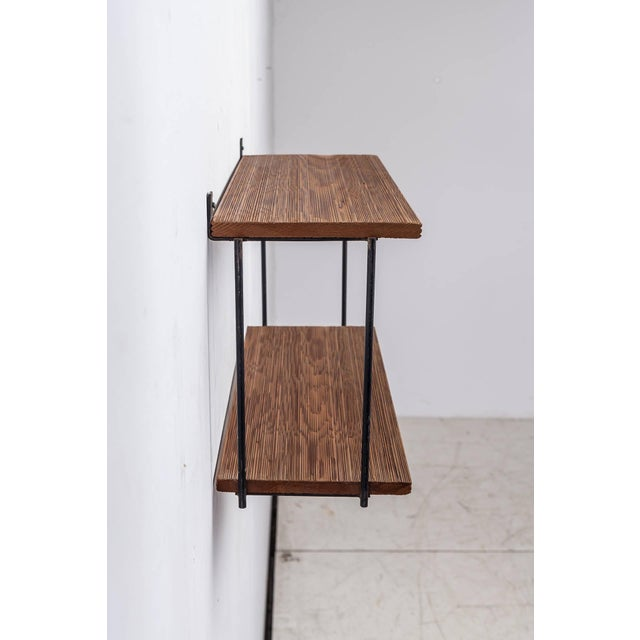 A shelving unit by Muriel Coleman, made of a black iron frame with two textured redwood shelves. The wood has a beautiful...