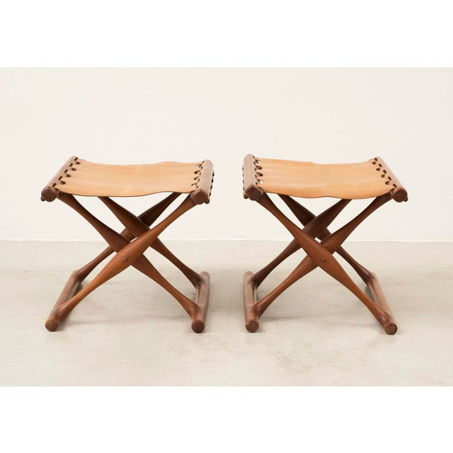 A handsome pair of matching Gold Hill Stools by Poul Hundevad. Bases in teak, with nicely patinated camel leather....