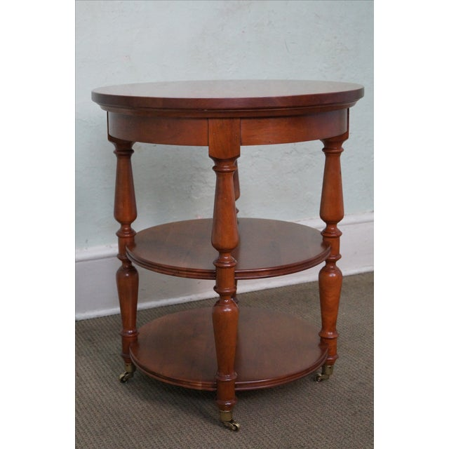 High-quality, American-made, circular side table crafted of solid cherry wood. This three-tier table is situated on...