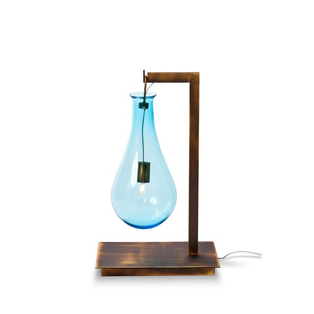 Versonese Drop single light table lamp is available in a variety of metal finishes as well as a variety of glass colors.