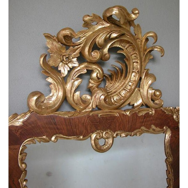 A curvaceous Danish rococo style burl walnut and carved giltwood mirror with exuberant rocaille carving; with lively...
