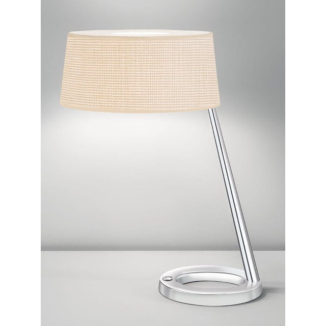Modern style lamp in chrome. Oval hollow bases and tapered columns. Desk lamp has colour co-ordinated push switch in base....