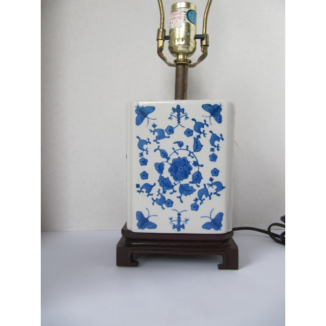 Beautiful blue and white square porcelain Chinoiserie lamp with butterflies and flowers on a wood stand. The stand has a...