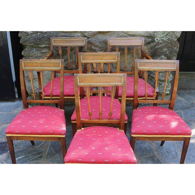An elegant set of six sturdy and very serviceable Continental chestnut wood neoclassical dining chairs with unusual carved...
