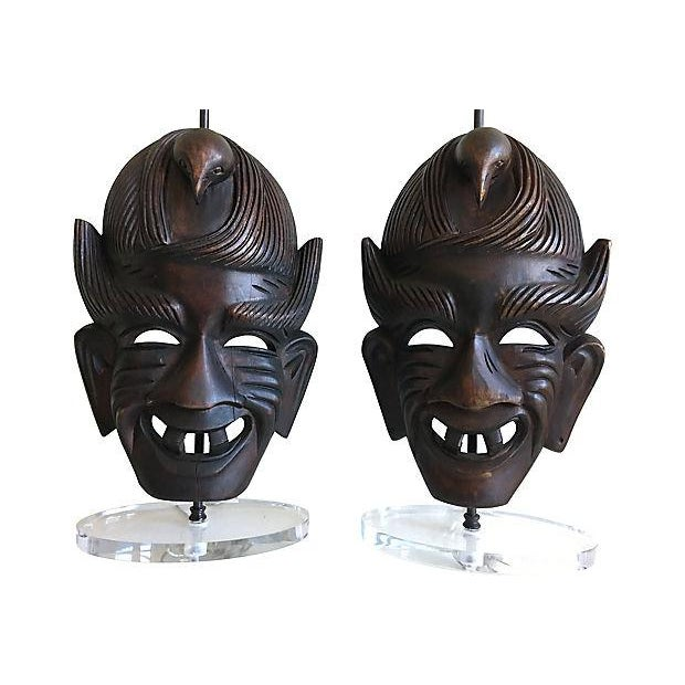 Exquisite pair of hand-carved wood African tribal mask lamps professionally mounted with steel fittings on custom oval...