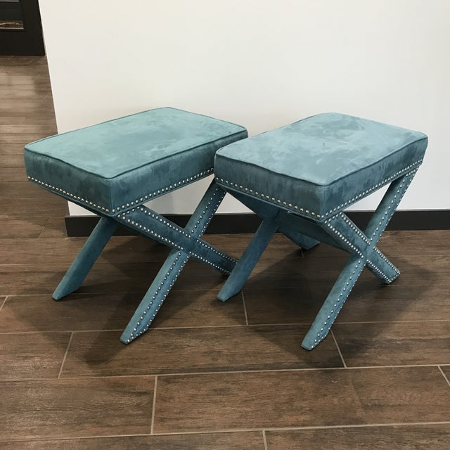 Pair of teal faux velvet ottomans with nailhead trim and X legs. Would look fabulous at the foot of a bed, in front of a...