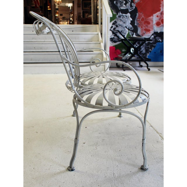 Stylized after Francois Carre with sunburst seats, vertical concave steel slat backs and wrought iron legs and curled arms.