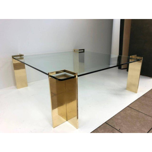 Polished bronze and glass coffee table. Glass is approximately one inch thick. Four individual bronze bases which weighs...