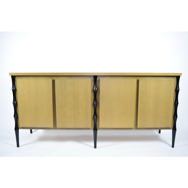 Beautiful Donghia inspired sideboard. Subtle bamboo style legs, four doors. Beautiful stain finish on wood.