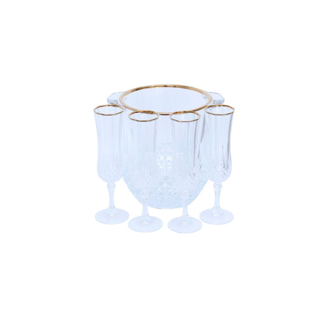 A cut glass champagne bucket with four matching champagne flutes. The top rims are gilt edged and the the glass is diamond...