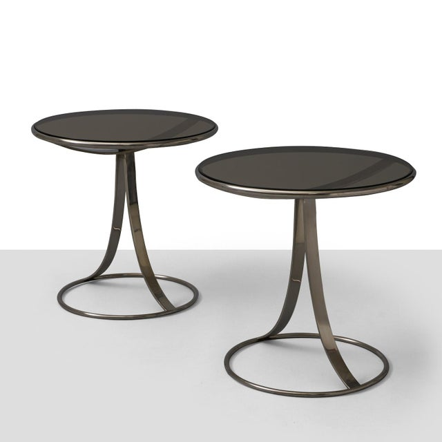 A pair of steel and smoked glass occasional tables designed by Gardner Leaver for Steelcase.