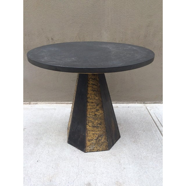 The table has a braised bronze and blackened steel base. The slate top rests upon a steel base which is attached to an...