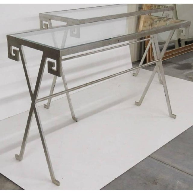 Pair of Mid Century Modern silvered glass top console tables. Tables are silvered iron with beveled glass tops.