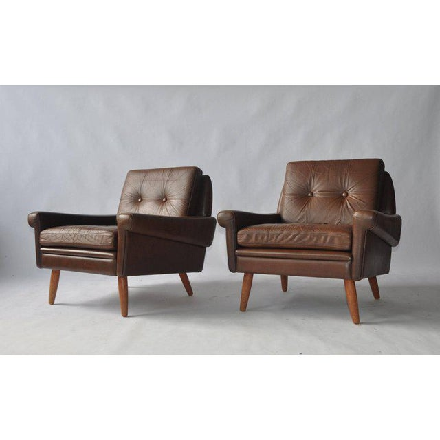 Pair of Svend Skipper leather lounge chairs. Stained oak legs.