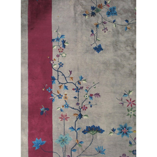 A wonderful example of a Chinese hand woven art deco style rug with magnificent flower heads on vines weaving onto both...