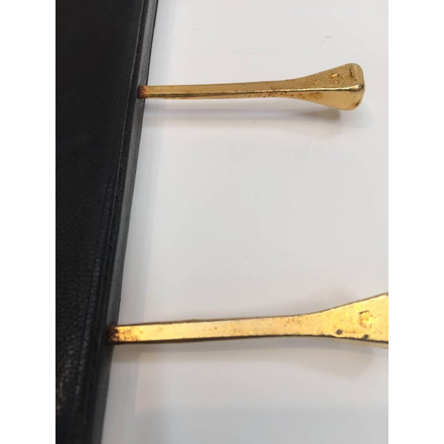 Elegant leather and brass tie rack by Longchamp, Paris, France, 1960s. In the style of Jacques Adnet, black leather tie...
