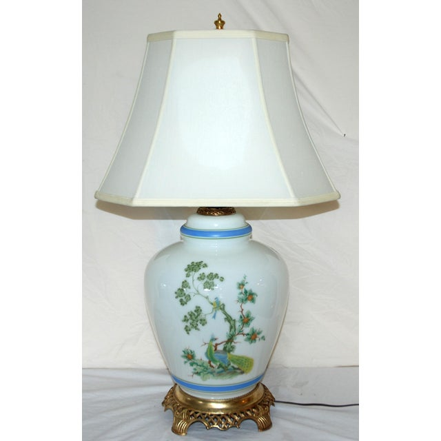 A large Asian style lamp decorated with peacocks on three sides. There is a night light in the base and the lamp works...