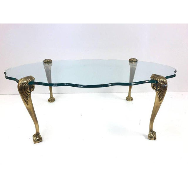Brass claw and ball glass top coffee table. Heavy solid brass legs with a scalloped edge beveled glass.