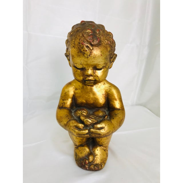Lovely Venetian style chalkware statuary of a small child holding a bird. The piece is from the 1960s.