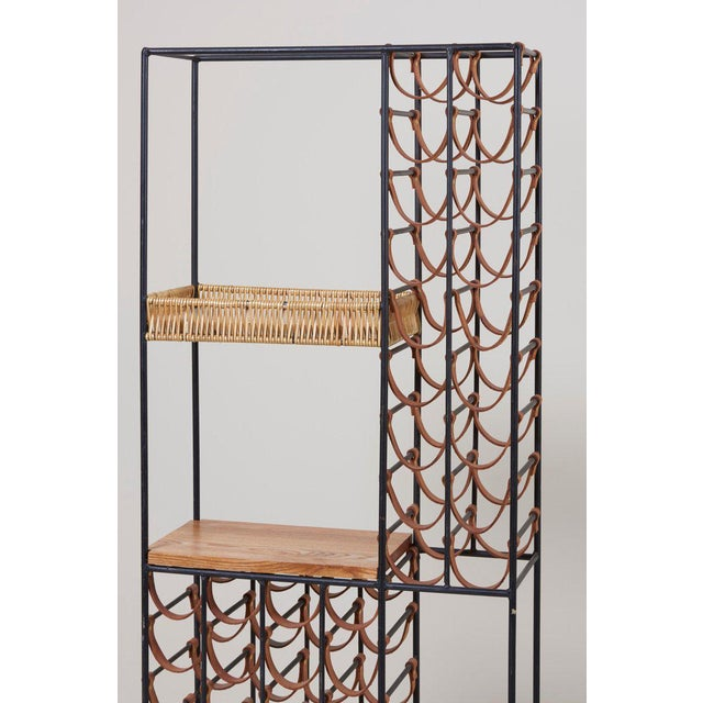 Large tower wine rack designed by Arthur Umanoff, made of wrought iron with leather straps. Solid iron frame with three...