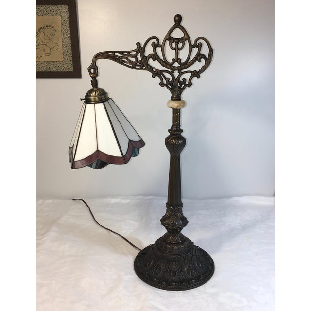 Unusual bridge table lamp with stained glass shade. It is in excellent working condition. The stone knob in the stand has...