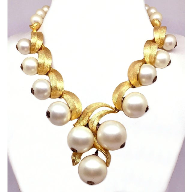 Circa 1950s to 1960s gold tone metal adjustable bib-style necklace with a gold tone, brushed metal leaf design. It is...