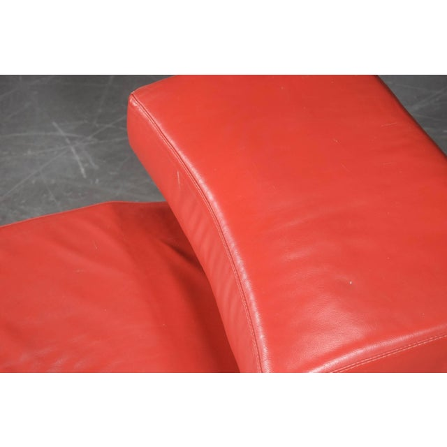 Chaise longue chair upholstered with red faux leather on a chromed steel frame.