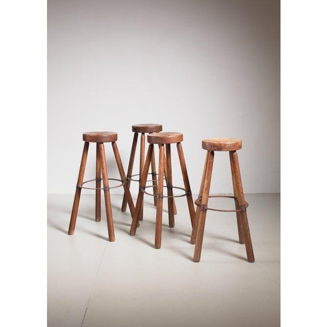 A set of four modernist French high stools in the manner of Pierre Jeanneret, made of teak with a metal foot ring. The...