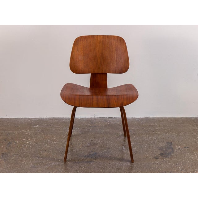 Gorgeous pair of early Eames DCW Dining Chairs in walnut. An ergonomic dining chair that is attractive as is comfortable...