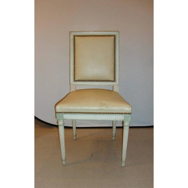 A Louis XVI style side chair by Maison Jansen, the chair has studded lining throughout in a distressed cream paint color.