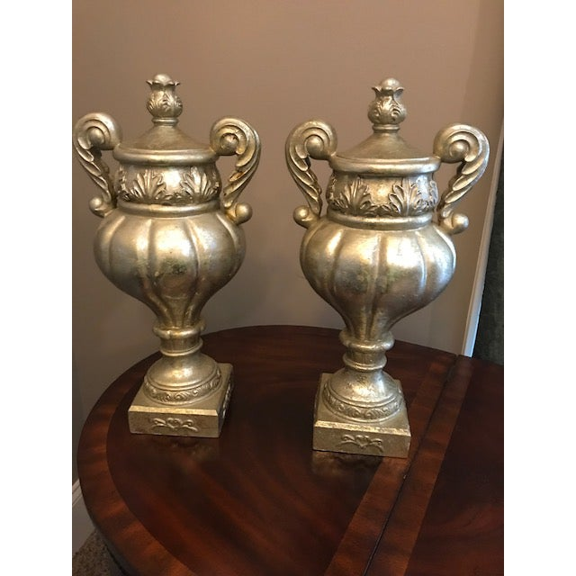 A pair of stylish, metallic gold and silver finish Grecian style urns. Lovely home decor items for a mantle, office or...