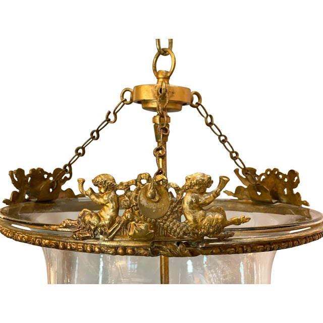 With eagle suspended clasping a ring and chain that suspends the glass jar suspended on three chains, the top gilt brass...
