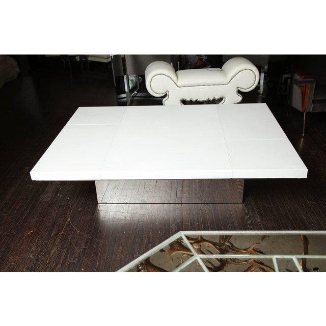 Chic white leather cocktail table with stitching detail on a mirrored stainless steel base.