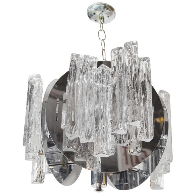 Mid-century modern trilateral chandelier with ice glass details. The fixture is comprised of a chrome frame with circular...