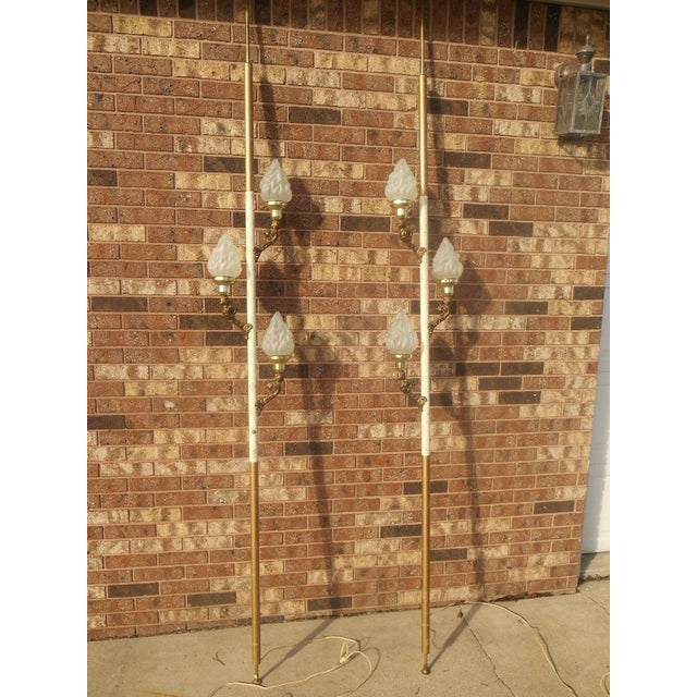 Pair Mid-Century Hollywood Regency tension pole lamps. These lamps have brass cherubs holding up 3 satin glass flame...
