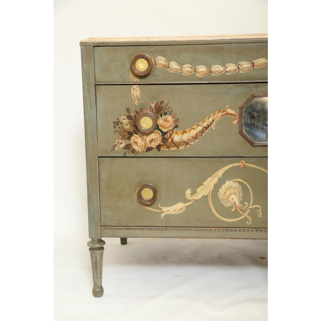 Commode having a molded top of faux marble its case hand-painted with classical motifs of cornucopias scrollwork and...