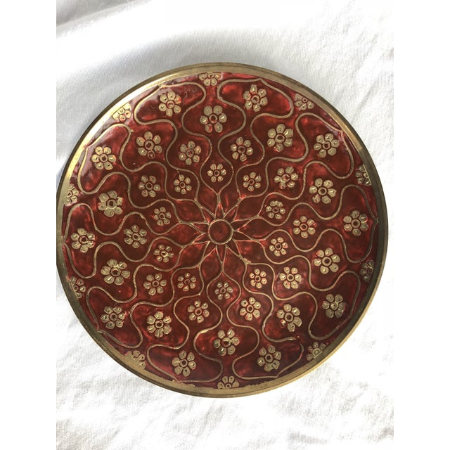 A lovely vintage enamel brass plate. Features a deep red color amongst a pattern of flowers and lines. Contains hanging...