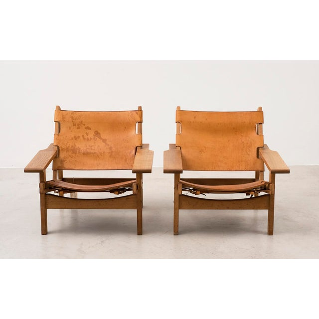 A pair of solid oak easy chairs, seat and back with patinated natural leather by Kurt Ostervig. Manufactured by K. P....