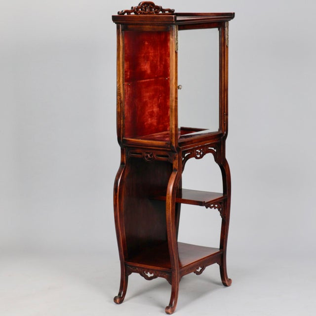 Chinese display cabinet has open work carved crest, upper glass front cabinet with brass ornaments, red velvet lining and...