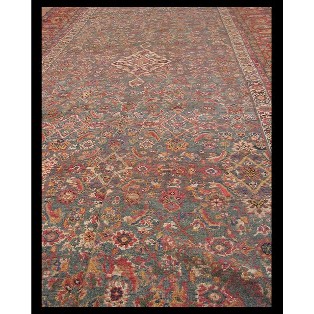 Antique NW Persian Rug with an ivory background and patterned border.