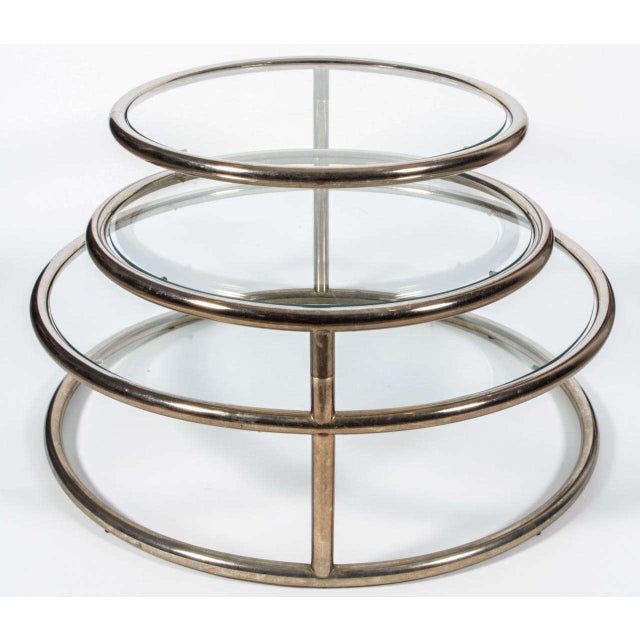 Chic brass and glass circular cocktail table with three tiers that swivel to expand to reach all your guests. USA, circa...